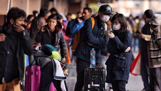 कोरोना विषाणूच्या पार्श्वभूमीवर तोंडावर मास्क लावून रेल्वेची माहिती घेताना परदेशी पर्यटक