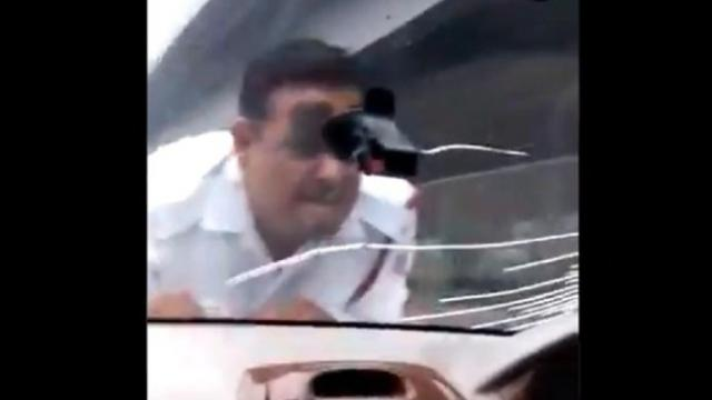 वाहनचालक वाहतूक पोलिसाला आपल्या गाडीच्या बोनेटवरून पुढे नेताना